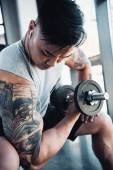 concentrated young sportsman exercising with dumbbell in gym
