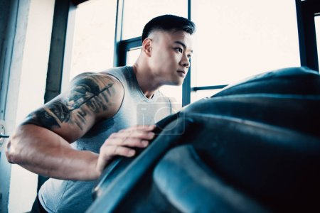 handsome young sportsman flipping heavy tire at gym