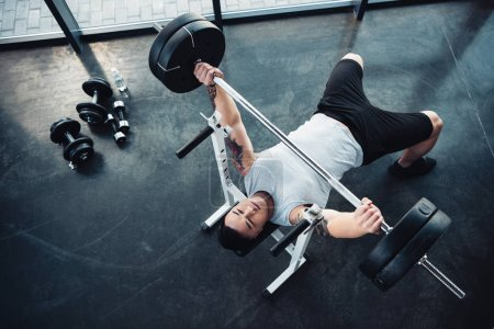 Photo for Top view of concentrated sportsman training with barbell at gym - Royalty Free Image