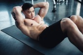handsome young sportsman with bare chest doing abs exercise on fitness mat at gym