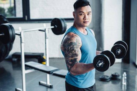 Photo pour Concentré jeune asiatique sportif exercice avec haltères en salle de gym et en regardant caméra - image libre de droit