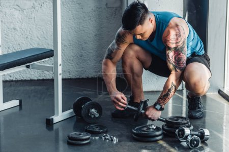 tattooed sportsman assembling dumbbells at gym