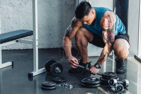 tattooed sportsman assembling dumbbells at gym