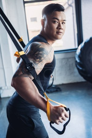 concentrated young asian muscular sportsman training with resistance bands in gym