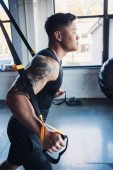 side view of young muscular sportsman training with resistance bands in gym