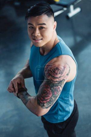 Photo pour Jeune sportif asiatique tatoué au gymnase de regarder la caméra - image libre de droit