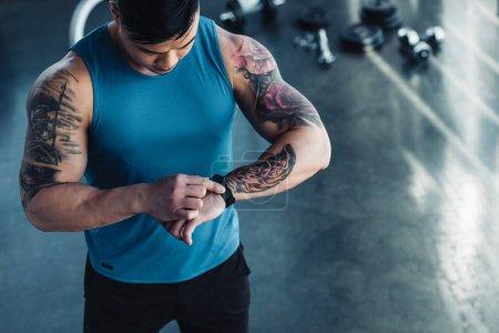 Ausgeschnittene Ansicht eines tätowierten jungen Sportlers im Fitnessstudio, der auf die Uhr schaut