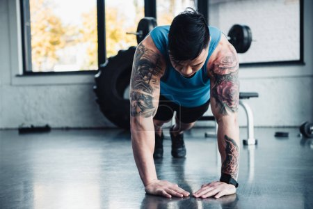 focused young sportsman doing plank exercise at gym