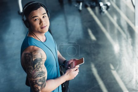 young asian sportsman using smartphone with graph on screen and listening to music