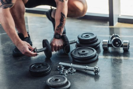 partial view of tattooed sportsman assembling dumbbells