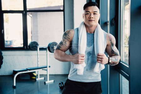 young asian sportsman with towel after long workout