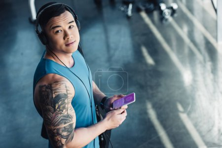 young asian sportsman using smartphone with shopping app and listening to music