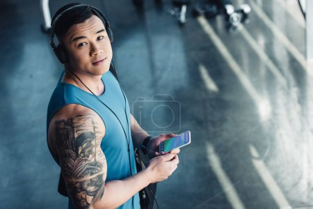 Photo for Young asian sportsman using smartphone with booking app and listening to music - Royalty Free Image