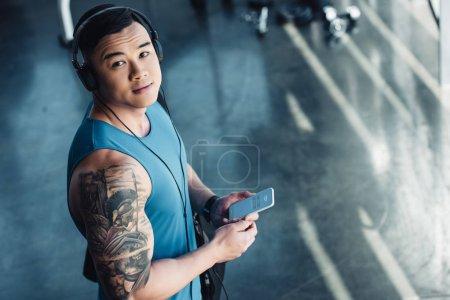 Photo pour Jeune sportif asiatique à l'aide de smartphone et écouter de la musique - image libre de droit