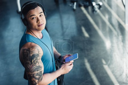 young asian sportsman using smartphone and listening to music