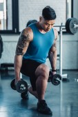muscular young sportsman exercising with dumbbells in gym
