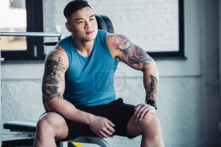 Photo for Muscular asian young sportsman sitting at gym - Royalty Free Image