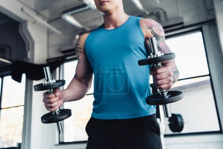 partial view of young sportsman exercising with dumbbells in gym