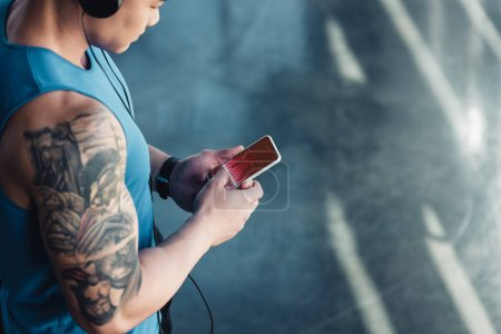 young sportsman using smartphone with graph on screen and listening to music