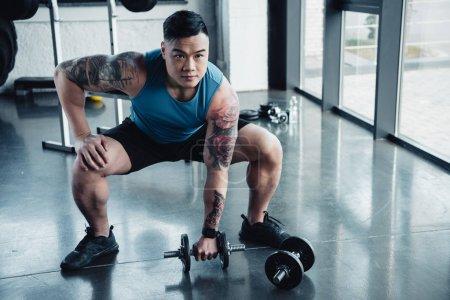 Photo pour Concentré de jeune sportif exercice avec des haltères dans la salle de gym - image libre de droit