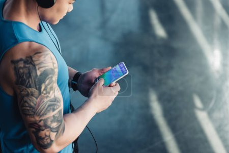 young asian sportsman using smartphone with booking app and listening to music