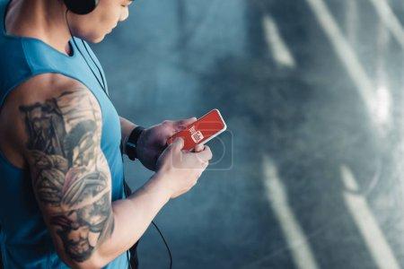 Photo pour Vue recadrée d'un jeune sportif utilisant un smartphone avec une application youtube et écoutant de la musique - image libre de droit