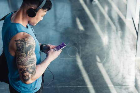 young sportsman using smartphone with health data appliance app and listening to music