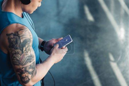 Photo pour Vue recadrée d'un jeune sportif utilisant un smartphone avec une application facebook et écoutant de la musique - image libre de droit