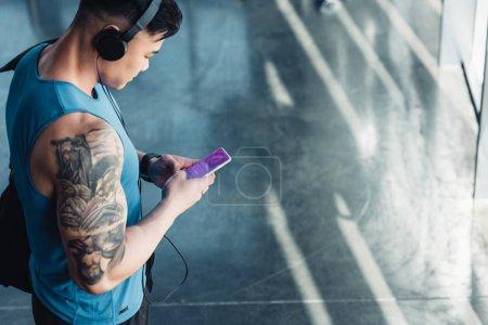 Photo pour Beau jeune sportif utilisant un smartphone avec une application shopping et écoutant de la musique - image libre de droit