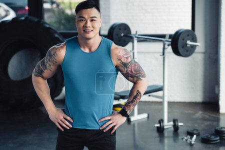 young asian sportsman looking at camera with hands on hips at gym