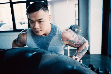 close up of young asian sportsman flipping heavy tire at gym
