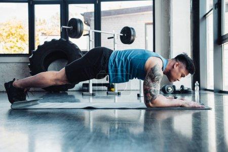 vue latérale du jeune sportif, faire de l'exercice de la planche au gymnase