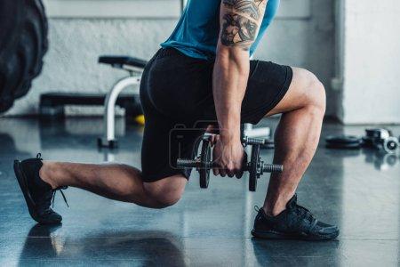 Photo pour Vue partielle du jeune sportif exercice avec des haltères dans la salle de gym - image libre de droit