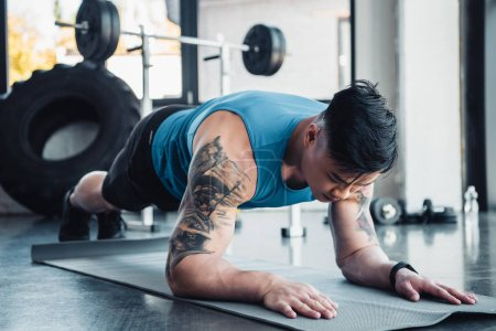 young sportsman doing plank exercise on gym mat