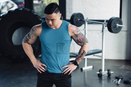 Photo for Young asian sportsman with hands on hips at gym - Royalty Free Image