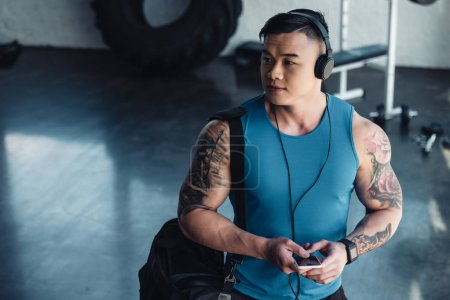 young asian sportsman using smartphone and listening to music in gym