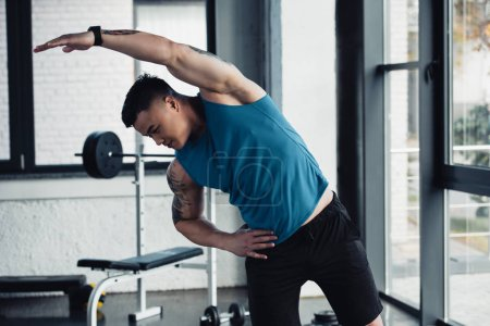 young sportsman doing stretching exercise at gym