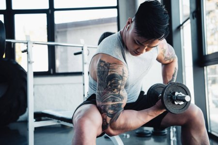 muscular young sportsman exercising with dumbbell in gym