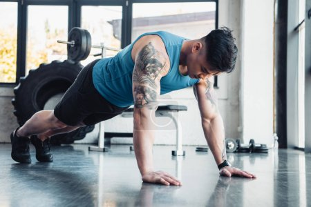 muscular young sportsman doing plank exercise at gym