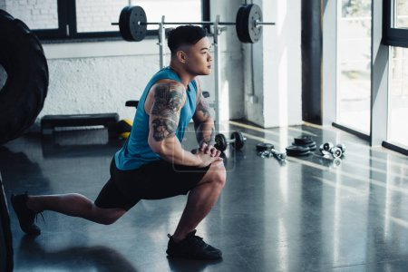 focused young sportsman doing lunge exercise at gym