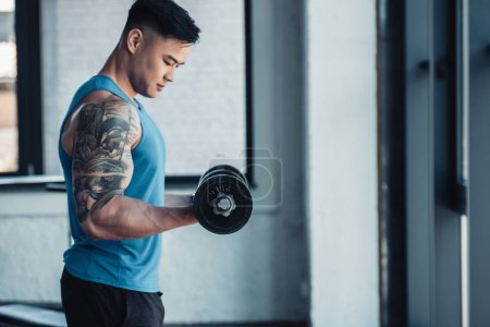 concentrated side view of young sportsman exercising with dumbbell in gym