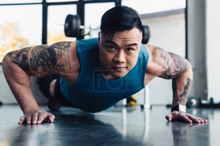 focused young asian sportsman doing plank exercise at gym