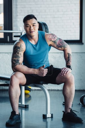 smiling young asian sportsman sitting at gym and looking at camera