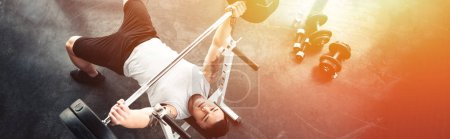 muscular sportsman exercising with barbell at gym in sunlight