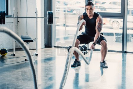 young asian sportsman working out with battle ropes at gym