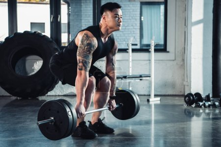 muscular tattooed sportsman training with barbell at gym