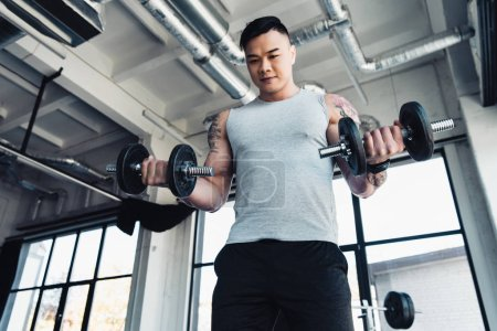 concentrated young asian sportsman exercising with dumbbells in gym