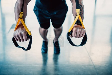 cropped view of young muscular sportsman training with resistance bands in gym