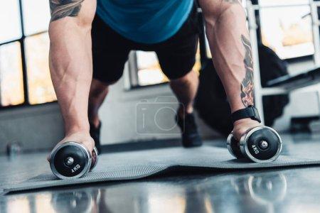 Photo pour Vue partielle du jeune sportif exercice avec des haltères dans la salle de gym sur le tapis de sport - image libre de droit