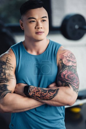 portrait of muscular young asain sportsman at gym wearing blue